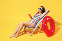 Full Body Length Happy Young Woman Wear Red Blue Swimsuit Sit On Wooden Chair Hold Use Mobile Cell Phone Isolated On Vivid Yellow Color Background Studio Summer Hotel Pool Sea Rest Sun Tan Concept
