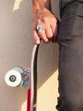 Crop Skater With Skateboard On Beige Background