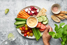 Plated Of Assorted Healthy Fresh Vegetables With Hummus Served On Table Near Bread