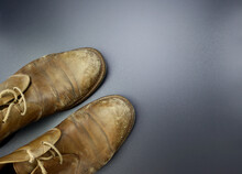 Old Worn Boots Made Of Genuine Leather. Shabby Men's Shoes On A Gray Background.