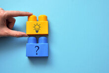 Designer With A Picture Of A Question And A Light Bulb. The Symbol Of The Emergence Of Questions And The Search For Solutions To Them