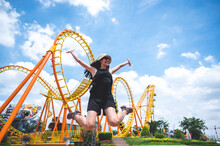 A Women Has Fun Happy Joy Day At Amusement Park In Summer Sunny Day, Roller Coaster, Jumping Girl, Vacation Leisure Holiday, Activities Concept. Asian Women, Nice Clear Blue Sky. Enjoy Moment