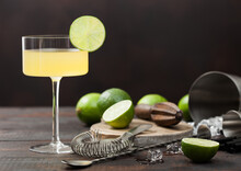 Gimlet Kamikaze Cocktail In Modern Glass With Lime Slice Wood Board With Fresh Limes And Strainer With Shaker