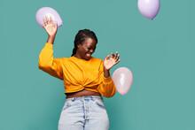 Joyful Black Woman Playing With Balloons In Studio