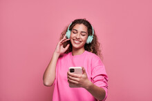 Smiling Woman Listening To Music And Using Smartphone