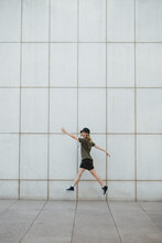 Happy Woman Jumping Over Urban Pavement Against Wall