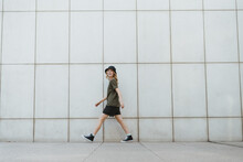 Happy Woman Walking Over Urban Pavement Against Wall