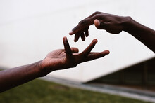 Black Friends Reaching Hands To Each Other