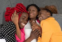 Happy Black Girlfriends Cuddling On Concrete Ground