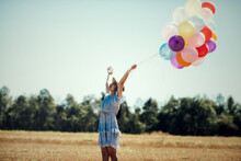 Portrait Of A Happy Young Woman With Colorful Latex Balloons, Outdoor