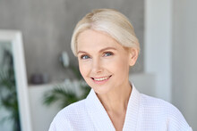 Portrait Of Happy Smiling Beautiful Middle Aged Woman Wearing Bathrobe At Spa Salon Hotel Looking At Camera. Advertising Of Bodycare Spa Procedures Antiage Delicate Dry Skin Care Products Concept.