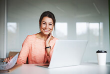 Young Attractive Female Business Analyst In Pink Jacket Working At The Laptop In Cozy Luxury Office Interior
