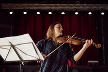 Professional Female Violinist Performing In Concert Hall