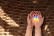 Manos Abierta De Niña Reflejando Luz De Arcoiris En Las Palmas De Sus Manos Sobre Fondo De Mimbre Horizontal