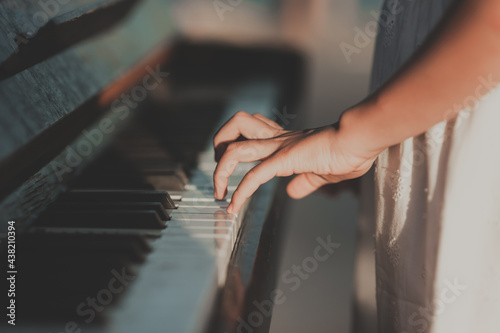 Obraz na plátně Female hands press the keys on the piano. Outside