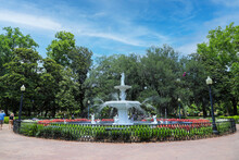 A Circular White Water Fountain In The Park  Surrounded By Colorful Flowers And Lush Green Trees And Plants With People Walking And Sitting Around The Fountain At Forsyth Park In Savannah, Georgia