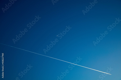 Fototapeta Moon and airplane on a blue darker sky.