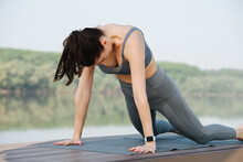 Hardy Woman Doing Yoga Outdoors In A Beautiful Spot On A Riverside