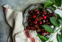 Overhead View Of Fresh Cherries On A Pewter Plate Next To A Tea Towel And Foliage
