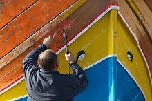 Rear View Of A Man Stripping Paint Off A Traditional Luzzu Boat With A Blowtorch, Marsaxlokk, Malta