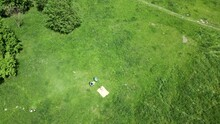 Woman Sunbathes On A Green Meadow. Lying On His Stomach, On A Yellow Rug. A Drone Flies Over Her. Aerial Photography.