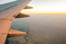 View From Airplane On The Aircraft White Wing Flying Over Desert Landscape In Sunny Morning. Air Travel And Transportation Concept.
