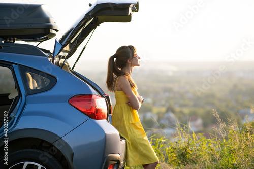Obraz na płótnie Happy woman driver in summer dress enjoying warm evening near her car