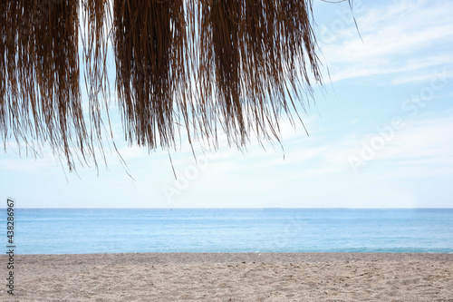 Beautiful sandy beach near tranquil sea, view from under hut with straw roof Fototapet