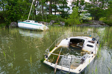 Stockholm, Sweden Two Abandoned Sailboats Sit In Shallow Water In Lake Malaren.