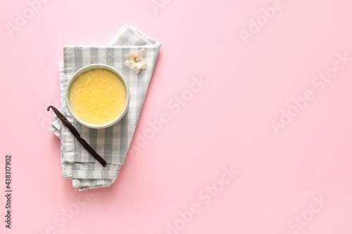 Fototapeta Ramekin with tasty vanilla pudding on color background