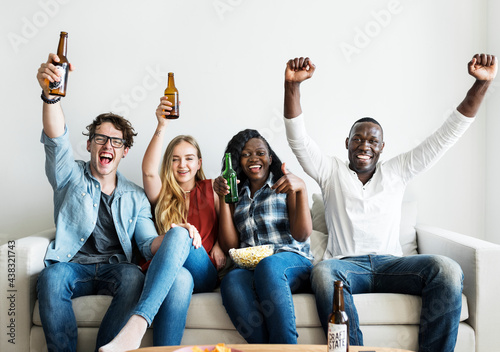 Foto Group of diverse friends drinking and cheering while watching sports together