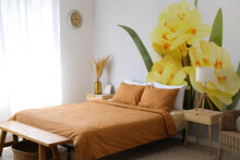Stylish Interior Of Bedroom With Beautiful Narcissus Flowers On Wall