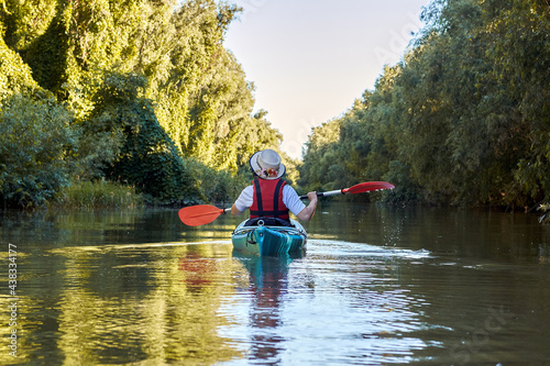 Fotografia Back view on woman row in blue kayak at wilderness areas of Danube river near gr