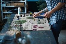Male Herbalist In Plaid Shirt Making Herbarium At Home