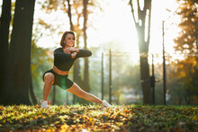 Attractive Smiling Woman With Brown Hair Stretching Legs During Morning Exercise At Local Park. Outdoor Sport Activity And Regular Training Concept.