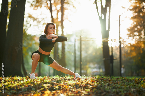 Billede på lærred Attractive smiling woman with brown hair stretching legs during morning exercise at local park