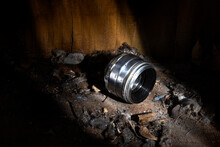Old Lens On A Pile Of Dirt And Dust Against The Background Of Old Walls Made Of Hewn Boards In A Beam Of Light