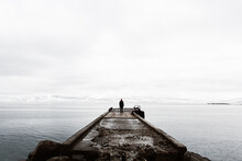 Traveler On Old Pier In Cold Seascape