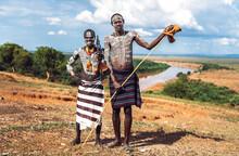 Two Men With A Machine Gun Standing Near Omo River On Karo Tribe