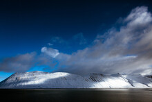 Clouds Over Snowy Mountains And Lake