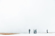 Anonymous People Walking In Snowy Countryside