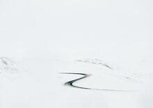 Curvy Road Through Snowy Field