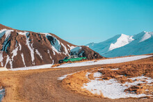 Car On Roadside In Snowy Mountains In Sunshine