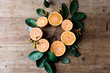 Amazing Circle Shaped Composition Of Orange Halves Among Green Leaves And Small Berries On Rustic Table