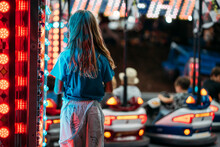 Little Cute Girl Standing Alone While Waiting Her Turn To The Crash Cars