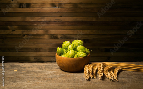 Fotografiet Oktoberfest beer barrel and beer glasses with wheat and hops on wooden table