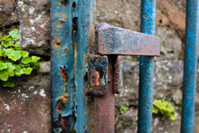 Old Blue Iron Gate Hinge  And A Old Stone Wall In The Background