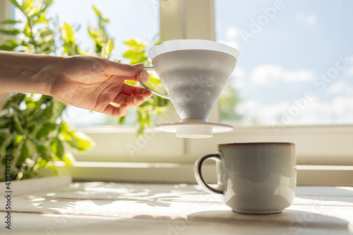 Canvastavla A female's hand removes a funnel with a filter from the cup
