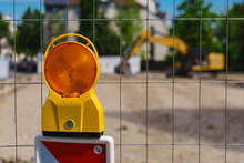 An Orange Warning Light On The Grating Enclosing A Construction Site. Selective Focus.