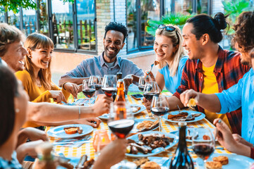 Group of friends having fun at bbq dinner outdoor in garden restaurant - Multiracial people eating food at barbecue backyard home party - Friendship, youth and party concept
